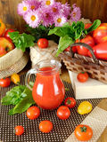 Tomato juice in a glass jug. Surrounded by tomatoes and green on a wooden background Royalty Free Stock Image