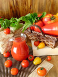 Tomato juice in a glass jug. Surrounded by tomatoes and green on a wooden background Royalty Free Stock Photography