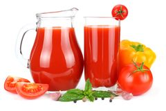 Tomato juice in glass jug with tomato, garlic, spices, and basil isolated on white background royalty free stock photography