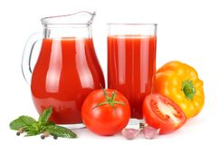 Tomato juice in glass jug with tomato, garlic, spices, and basil isolated on white background royalty free stock photo