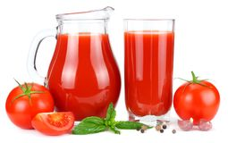 Tomato juice in glass jug with tomato, garlic, spices, and basil isolated on white background royalty free stock image