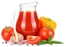 Tomato juice in glass jug with tomato, garlic, spices, and basil isolated on white background stock photos