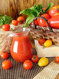 Tomato juice in a glass jug. Surrounded by tomatoes and green on a wooden background Stock Image