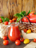 Tomato juice in a glass jug. Surrounded by tomatoes and green on a wooden background Royalty Free Stock Images