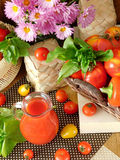 Tomato juice in a glass jug. Surrounded by tomatoes and green on a wooden background Stock Photos