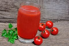 Tomato juice in a glass on rustic wooden table Royalty Free Stock Photo