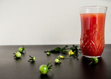 Tomato juice. Glass of tomato juice, tomatoes and leaves Royalty Free Stock Images