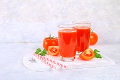 Tomato juice in glasses on a gray concrete table. Tomato juice in glasses on a gray concrete table Royalty Free Stock Photography