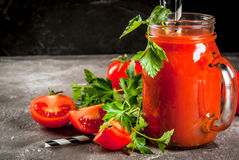Tomato juice in mason jar. With tomatoes and greens On a gray concrete table. Copy space Royalty Free Stock Image