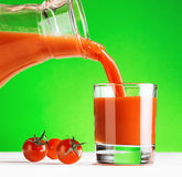 Tomato juice pouring from jug into a glass Stock Images