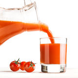 Tomato juice pouring from jug into a glass Royalty Free Stock Photography