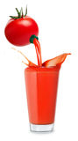 Tomato juice pours from tomato. Tomato juice pours from fresh tomato into big glass with splashes isolated on white background.  Fresh juice concept. Tomato Stock Image