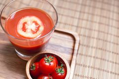A tomato juice smoothie and tomato vegetables on wooden board. Beverage for healthy and refreshment Stock Photos