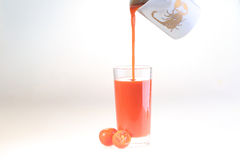 Tomato juice a stream flows in a transparent glass, a glass of t. Omato juice on a white background stock photography