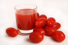 Tomato juice and tomatoes. Glass of tomato juice surrounded by tomatoes on white background Royalty Free Stock Photos