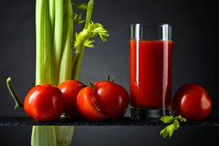 Tomato juice with tomatoes and celery sticks Royalty Free Stock Photos