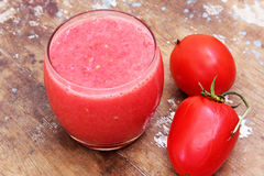 Tomato juice with tomatoes. Cup of tomato juice with tomatoes on wooden background Royalty Free Stock Images