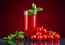 Tomato juice with tomatoes and green basil on black table stock image
