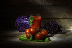 Tomato juice with tomatoes and vegetables. Still life with tomato juice, tomatoes and vegetables Royalty Free Stock Photos