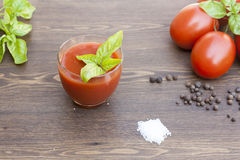 Tomato juice, tomatos, herbs and spices. On wooden table stock photography