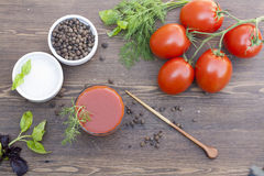 Tomato juice, tomatos, herbs and spices. On wooden table stock images