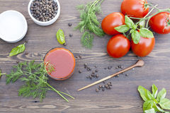 Tomato juice and tomatos. On wooden table royalty free stock images