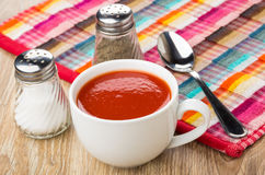 Tomato juice in white cup, salt, pepper, spoon. On wooden table Royalty Free Stock Images