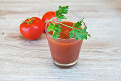 Tomato juice on the wooden table. Tomato juice and a sprig of parsley on the wooden table Royalty Free Stock Photo