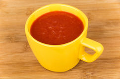 Tomato juice in yellow cup on table Royalty Free Stock Images