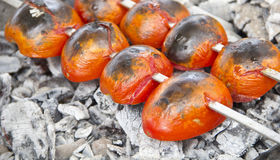 Tomato for kebab on fire. Tomato for Shish kebab on fire ready for lunch Royalty Free Stock Images