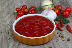 Tomato ketchup. Bright Tomato ketchup with herbs and spices on the wood background Royalty Free Stock Photography