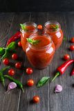 Tomato ketchup sauce with cherry tomatoes and red hot chili peppers, garlic and herbs in a glass jar on dark background. royalty free stock image
