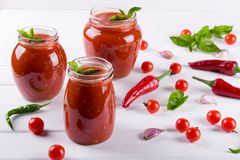 Tomato ketchup sauce with cherry tomatoes and red hot chili peppers, garlic and herbs in a  glass jar on white background. Royalty Free Stock Photos