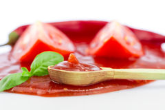 Tomato ketchup in a wooden spoon on a white background. Homemade Royalty Free Stock Photo