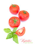 Tomato with leaf of basil isolated on white. shallow depth of field Stock Photo