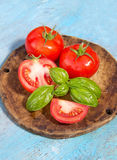Tomato with leaf of basil on a wooden shabby blue background Royalty Free Stock Image