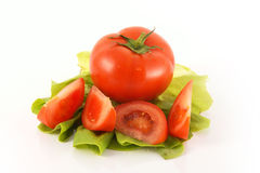 Tomato and lettuce. Tomato and tomato slices on a letuce leaf Stock Image