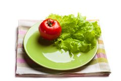 Tomato and lettuce on a dish. Red tomato and green lettuce on a dish Royalty Free Stock Photos