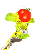 Tomato and lettuce on fork. Tomato and lettuce leaves on fork and measuring tape isolated on white background Stock Photography
