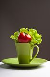 Tomato and  lettuce in a mug. Red tomato and green lettuce in a cup on a table Royalty Free Stock Photography