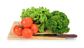 Tomato, lettuce and parsley on cutting board Royalty Free Stock Photos