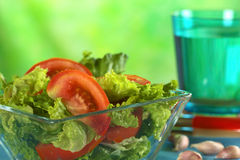 Tomato-Lettuce Salad. Fresh salad of lettuce and tomato with garlic and a glass of water in the back (Selective Focus, Focus on the tomato slice in the front Royalty Free Stock Images
