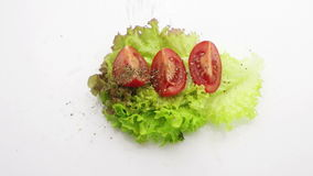Tomato on lettuce sprinkle with basil slow motion stock video