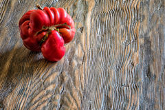 Tomato like a human head on wooden background with copy space.  Royalty Free Stock Images