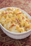 Tomato Macaroni and Cheese. Creamy baked macaroni and cheese with sun-dried tomatoes, provolone cheese, and mozzarella cheese, then topped with bread crumbs Stock Photo