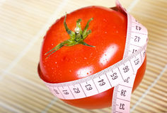 Tomato with measure Stock Photography