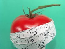 Tomato Measuring Tape. High resolution digital photo of a tomato and a measuring tape symbolize healthy diet, cancer/disease prevention and body weight control stock photography