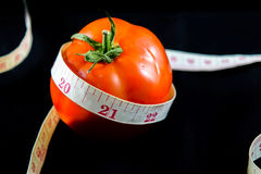 Tomato with measuring tape Royalty Free Stock Image