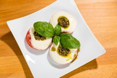 Tomato, Mozarella, Basil. Mediterranean style food: Grilled tomato with slightly melted mozarella cheese and basil pesto as well as basil leaves Stock Image