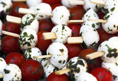 Tomato and mozzarella. Small cherry tomatoes and balls of mozzarella cheese on sticks stock image